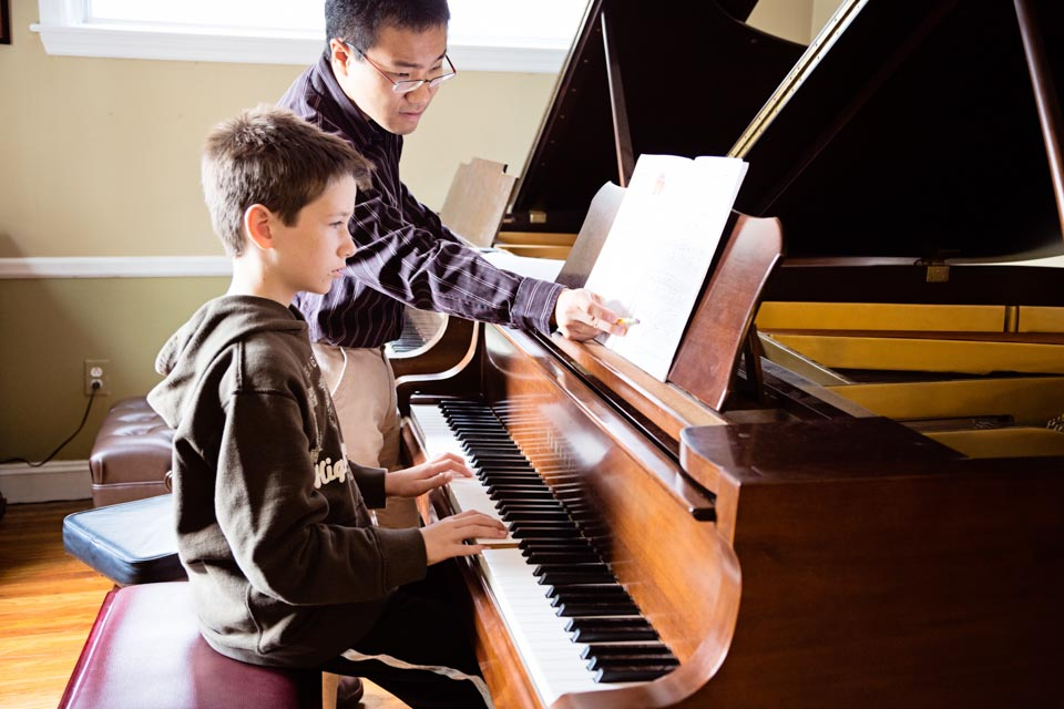Akira teaching piano lesson to a student